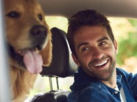 Man traveling with his dog in a car