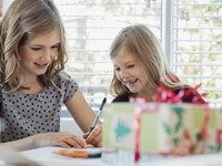 Kids wrapping Christmas gifts for others