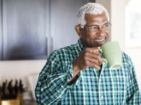 Confident man sipping coffee from a mug in his kitchen